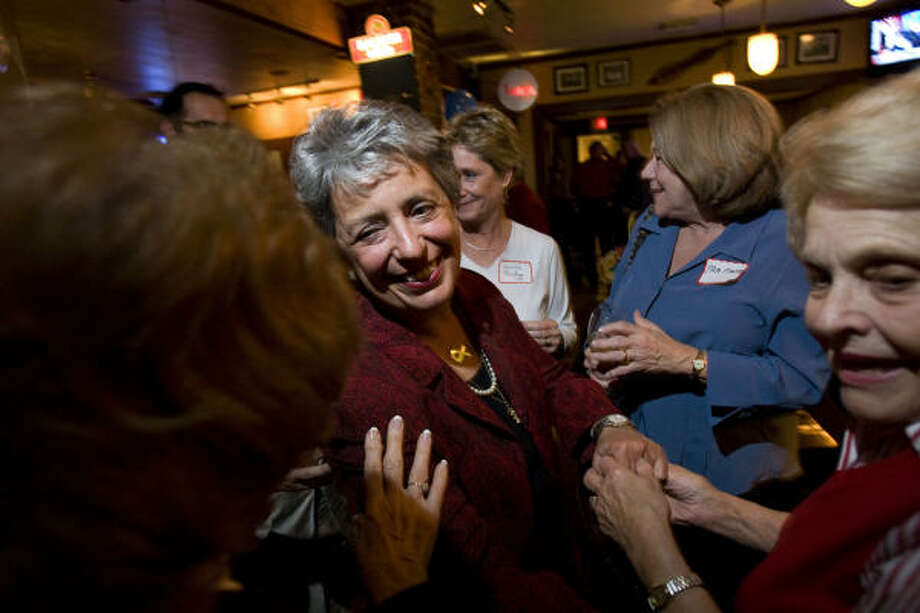 Pat Lykos, center, greets supporters Tuesday night while watching results in her close battle with C.O. Bradford for Harris County district attorney. Final, but unofficial, totals indicate that Lykos won. Photo: Johnny Hanson, Chronicle