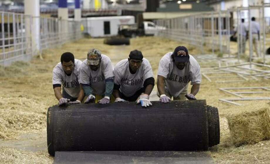 Workers disassemble animal pens Sunday in Reliant Arena. At the stadium, people are working around the clock to clear out the rodeo in time for the NCAA South Regional. Photo: JOHNNY HANSON, CHRONICLE