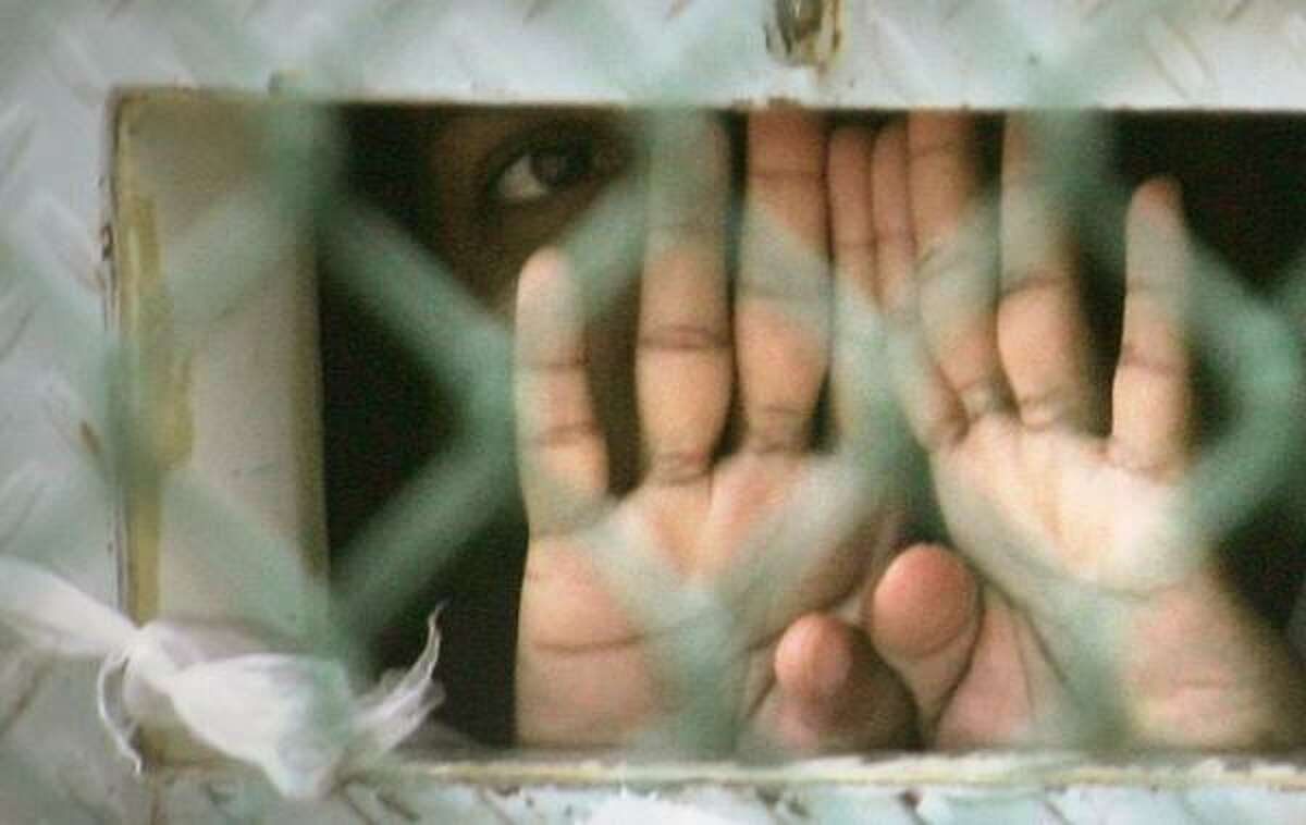 Thursday's Supreme Court ruling covers some 270 Guantanamo Bay detainees, like this one photographed in December 2006 through an opening in his cell door where food is passed through.