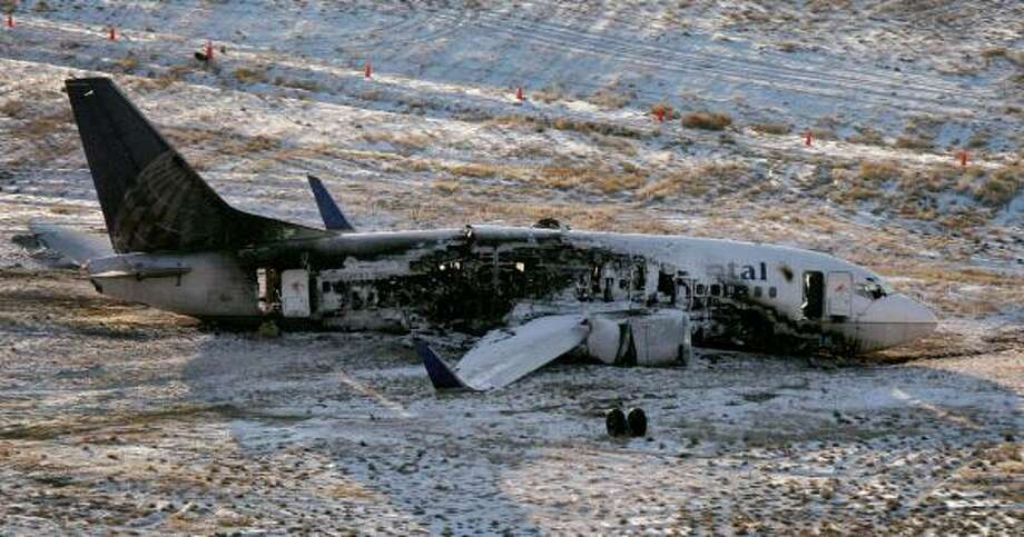 The badly charred remains of the Continental jetliner lie on the runway Sunday at Denver International Airport. Photo: PRESTON GANNAWAY, ROCKY MOUNTAIN NEWS