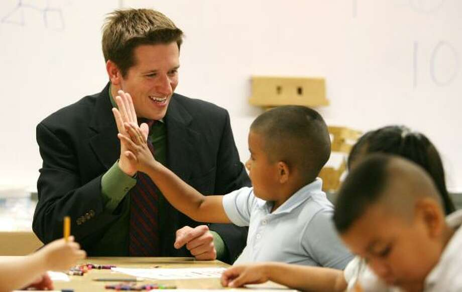 Port Houston Elementary School principal Reid Whitaker high-fives pre-K student Oscar Garcia. At 28, Whitaker is HISD's youngest principal. Whitaker was a Teach For America corps member at the school and returned to take on the role of principal. Photo: BILLY SMITH II, CHRONICLE