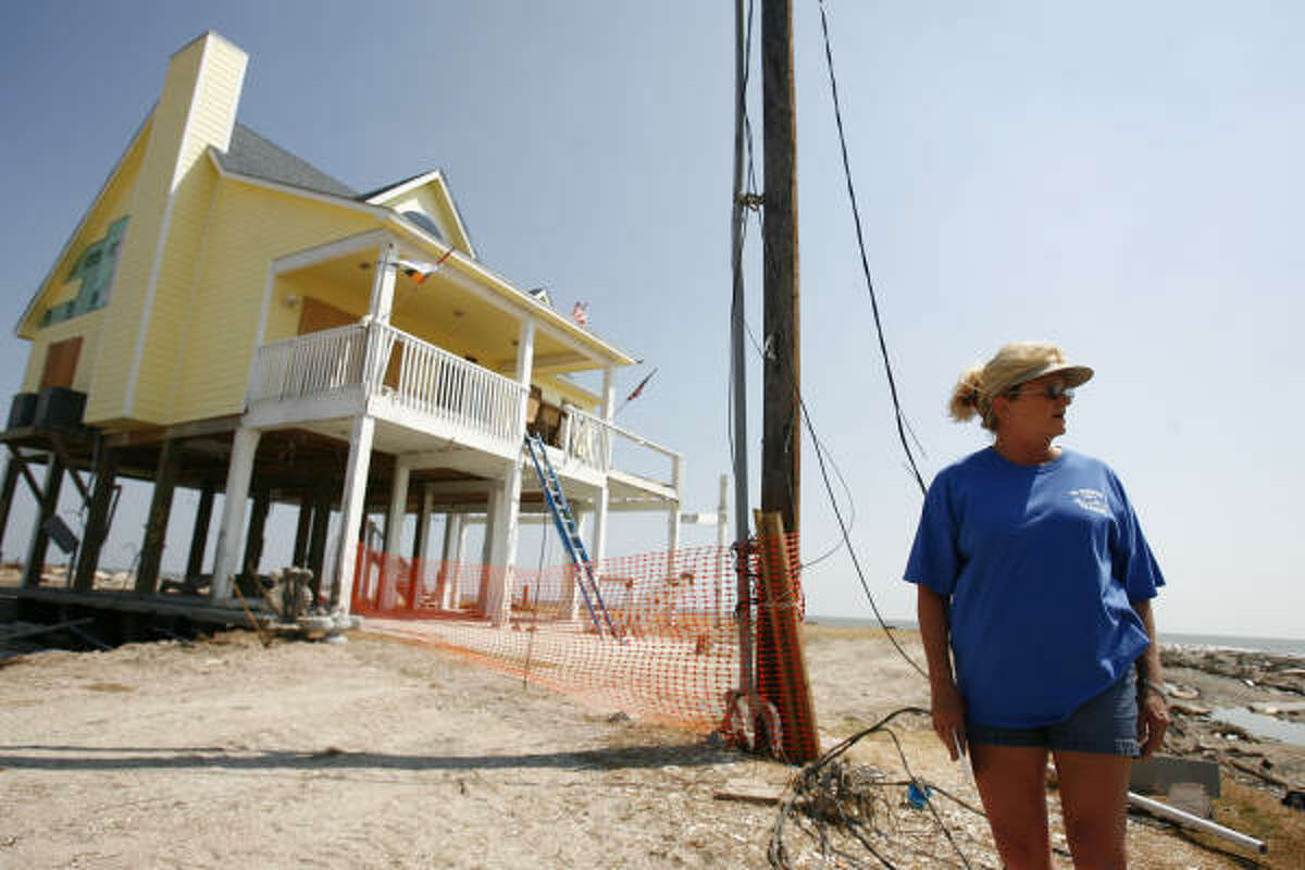 Pam Adams stands in front of her home in Gilchrist on Friday on the Bolivar Peninsula. Hurricane Ike leveled every house on the gulf side of Gilchrist, except hers. She and her Husband Warren Adams plan to rebuild and stay.