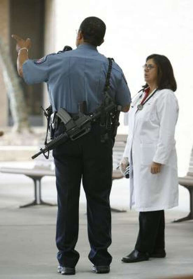 A UTMB officer guards Galveston's John Sealy Hospital with semiautomatic weapons as the hospital reopens Monday. Photo: JULIO CORTEZ, CHRONICLE