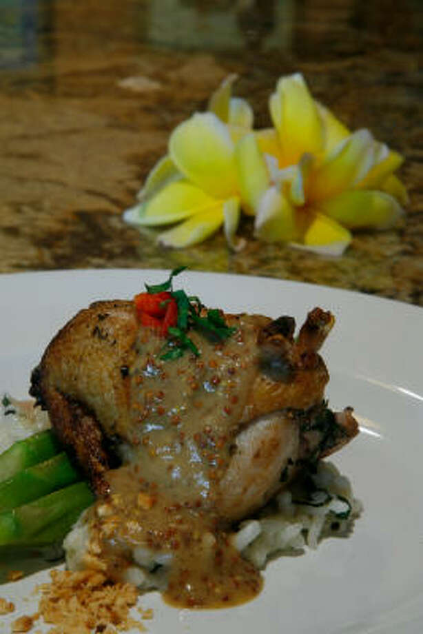 Plump, tender, pan-roasted quail rests on hazelnut risotto, asparagus and whole-grain mustard sauce. Photo: Steve Campbell, Chronicle