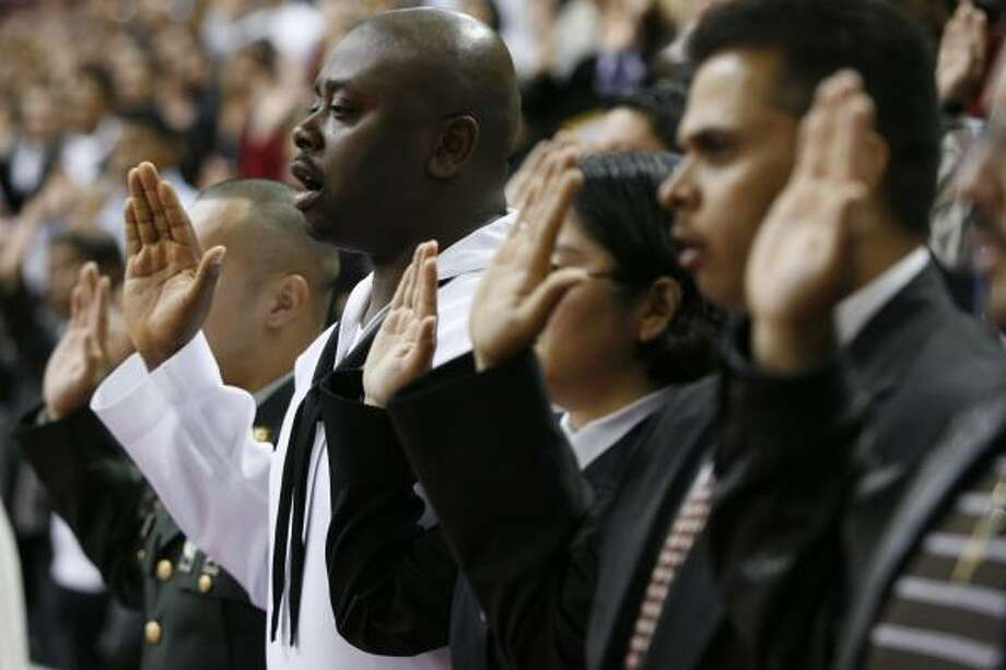 U.S. Navy medic Anthony Ozoemena, a native of Nigeria, swears allegiance to the United States and becomes a naturalized citizen during a ceremony Wednesday at the M.O. Campbell Center. He was one of more than 2,700 people from 112 nations to become naturalized. Photo: BRETT COOMER, CHRONICLE