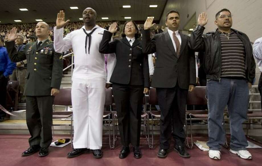 New citizens, from left, Mark Dejaico, Philippines; Anthony Ozoemena, Nigeria; Aixchelt Jarquin, Nicaragua; Adrian Polharel, Nepal; and Jesus Martinez, Mexico, take the oath of allegiance Wednesday. Photo: BRETT COOMER, CHRONICLE