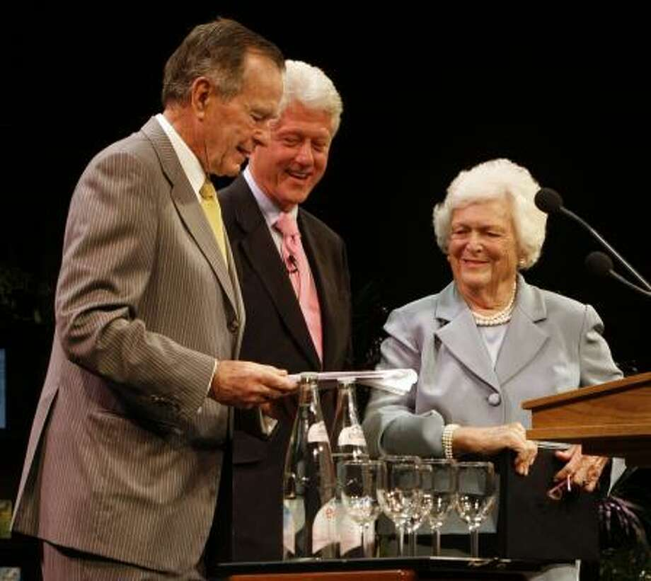 Former President Bill Clinton, center, was the surprise guest at a Celebration of Reading benefit hosted by former President George Bush and Barbara Bush at the Hobby Center for the Performing Arts. The benefit raised more than $2 million for literacy programs. Photo: KEVIN FUJII, CHRONICLE
