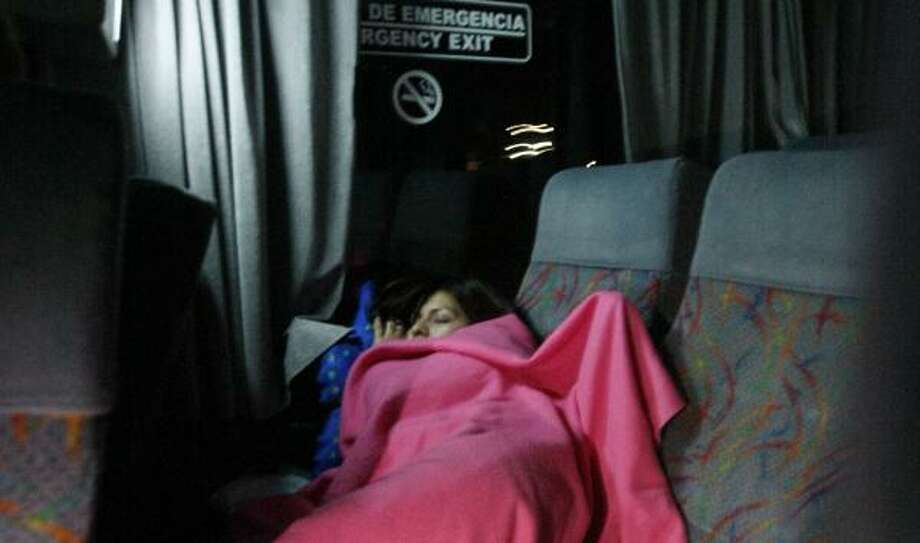 Aide Cantu naps on a bus trip from Monterrey, Mexico, to Houston to visit relatives. Fares are cheap but the ride can be risky. Photo: JULIO CORTEZ, CHRONICLE