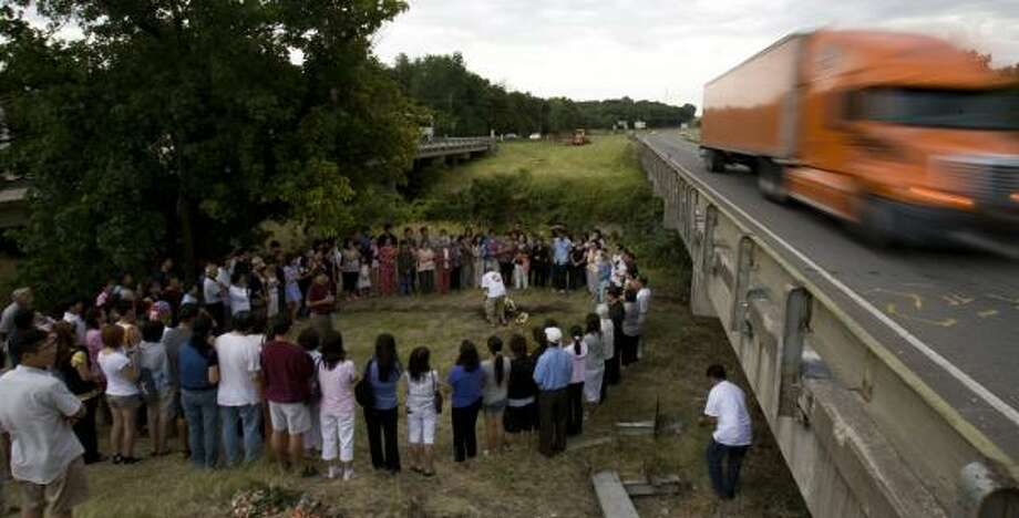 Worshippers returning Sunday from a Vietnamese Catholic religious festival in Missouri gather with other mourners at the site of the bus tragedy near Sherman. Photo: JOHNNY HANSON, CHRONICLE