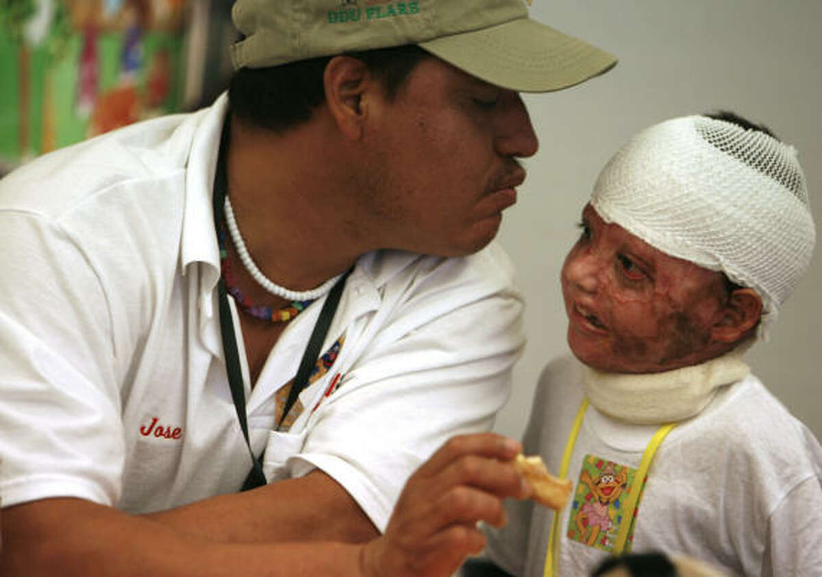 Burn survivor Mauricio Aguilar, 5, enjoys pizza with his father Jesus Aguilar, both of Mexico, during the After Burns Club support group meeting for burn victims and their families organized by Justina Page at Shriners Burns Hospital in Galveston on Saturday, Aug. 16.