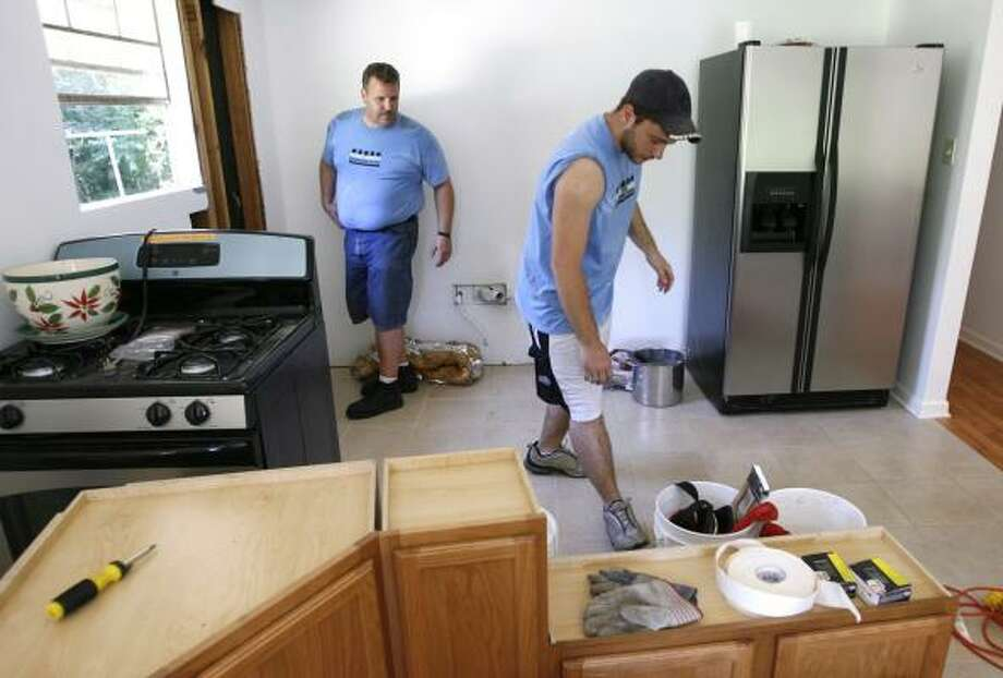 Church volunteers Rick Baker, left, and Rob Pratt get the kitchen ready for new cabinets to be hung in Betty Young's home in Lacombe, La. Groups of volunteers from the Ginghamsburg, Ohio, United Methodist Church have been helping Gulf Coast residents rebuild communities damaged during the hurricanes of 2005. Photo: ELLIS LUCIA, NEW ORLEANS TIMES-PICAYUNE