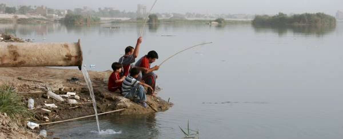 Iraqis fish in the Tigris River next to a sewage pipe this week in Baghdad.