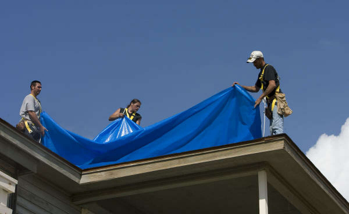 Workers install a tarp on an Ike-damaged house in Galveston's Palm Beach subdivision. The hurricane has prompted calls for reform of the Texas Windstorm Insurance Association.