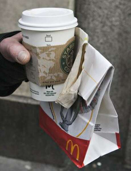 A New Yorker carries a Starbucks cup and and McDonald's bag. Starbucks earnings have been under pressure from gourmet coffee offerings from McDonalds and Dunkin' Donuts. Photo: JB REED, BLOOMBERG NEWS FILE