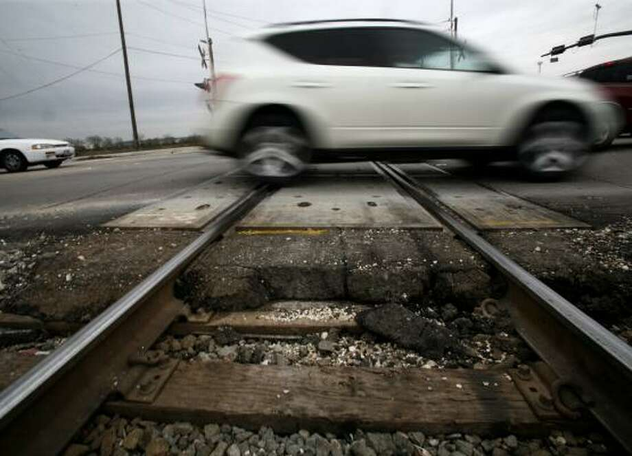 Vehicle traffic on Thursday crosses the rail line that runs parallel to Highway 90A in Stafford. Prompted by growing noise and traffic problems, a proposal would take freight rail traffic on one of Texas' oldest rail routes out of the major cities in Fort Bend County. Photo: STEVE UECKERT, CHRONICLE