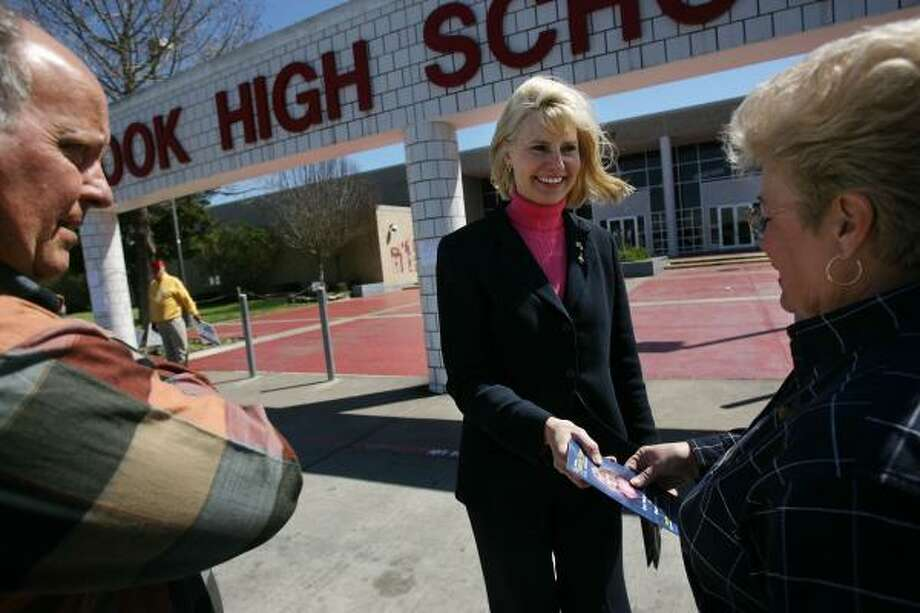 Shelley Sekula Gibbs greets voters Ron and Pherris Miller at Clear Brook High Tuesday. Photo: MAYRA BELTRÁN, CHRONICLE
