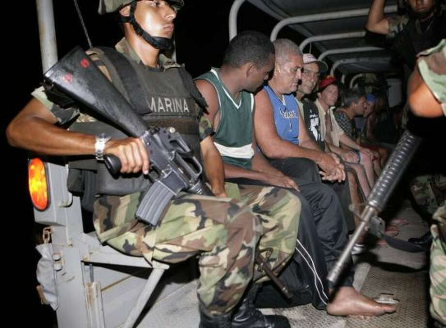 Cubans are escorted by Mexican navy soldiers after being arrested in Cancun on June 6. Photo: ISRAEL LEAL, ASSOCIATED PRESS