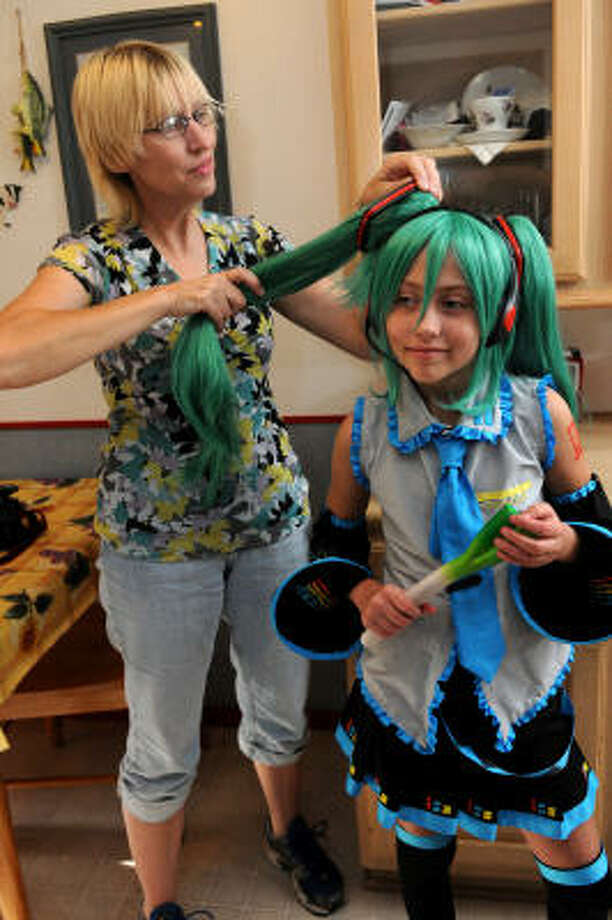 Maxine Ortner, 10, stands patiently in her Miku costume with her mom, Becky, at their home in Porter. Photo: Jerry Baker