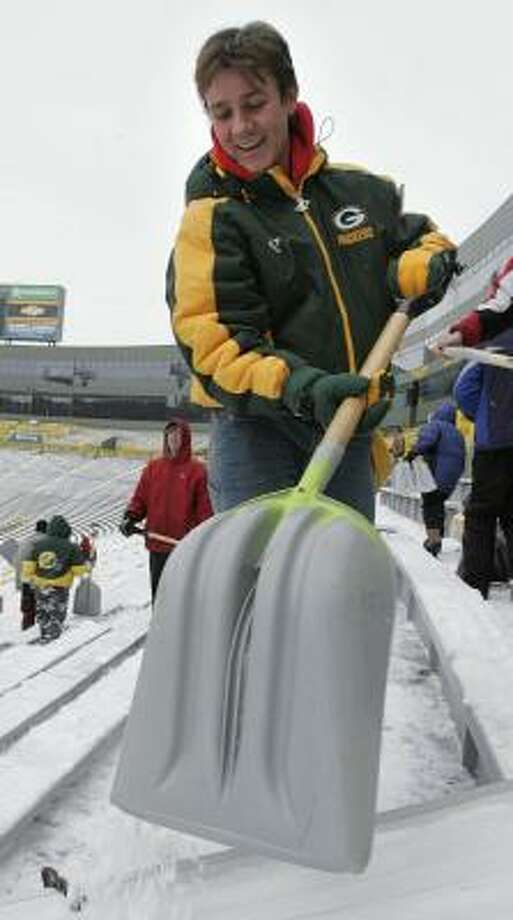 Wayne Scullino helps clear the ice and snow from the seats in Lambeau Field this week. Photo: RICK WOOD, AP