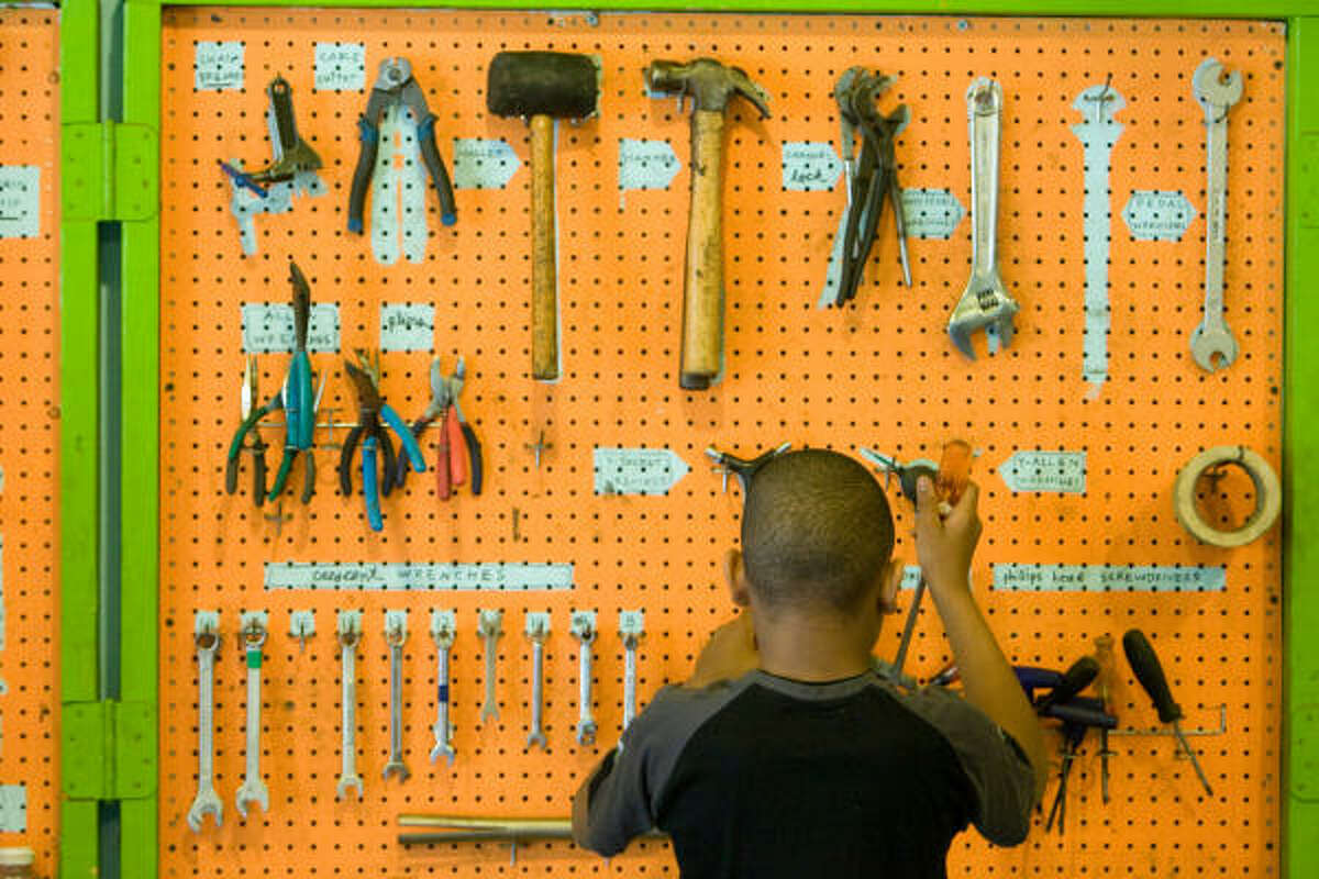 Kendrian Beverly, 11, selects a tool as he prepares to strip a bike for parts at the Third Ward Bike Shop in Houston.