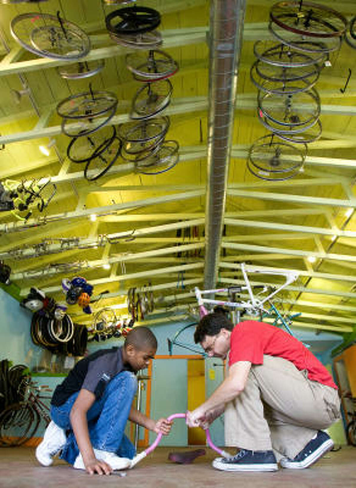 Kendrian Beverly, 11, and Jake Goldstein, a volunteer, strip a bike for parts at the Third Ward Bike Shop in Houston. Beverly fixed a bike for his sister for Christmas and built one for himself.