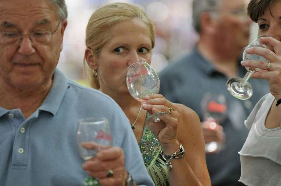 Attendees of the Galloping Grapes, A New York Wine Event, taste New York state wines at the Saratoga Race Course on Sunday Aug. 7, 2011, in Saratoga Springs, N.Y.  The event benefited the Times Union Hope Fund and Classroom Enrichment programs. (Philip Kamrass / Times Union) Photo: Philip Kamrass / 00014162A