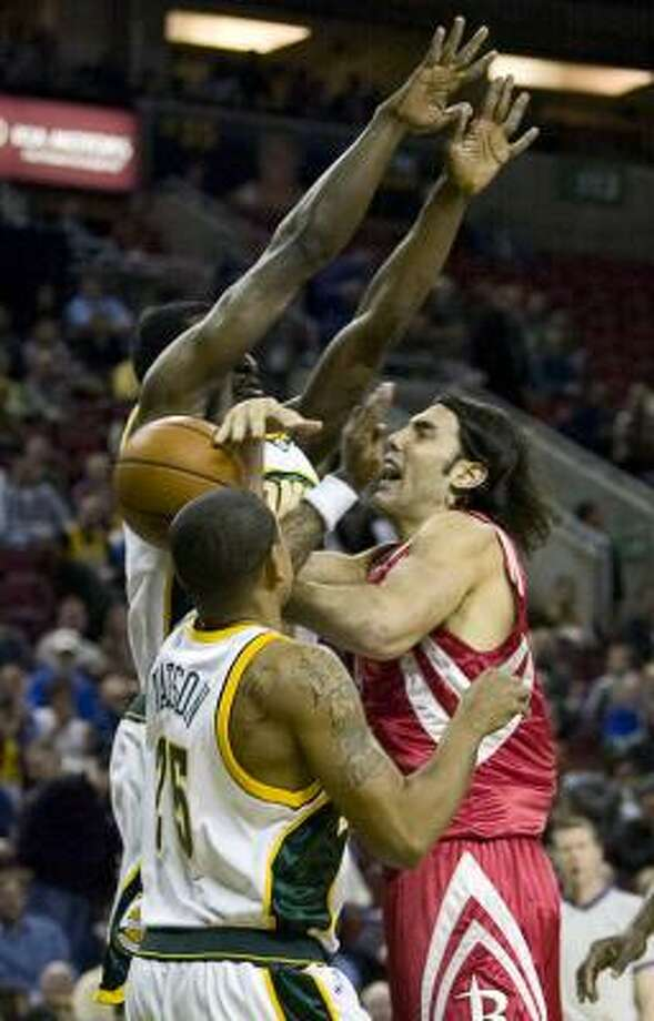 Rockets forward Luis Scola is fouled while going to the basket by the SuperSonics' Earl Watson, left, during the first half. Photo: Jim Bryant, AP