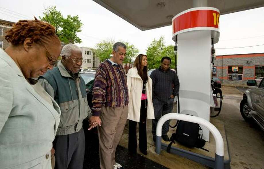 "Rocky Twyman, 59, center, leads members of the First Church of Seventh-day Adventists in a prayer for lower gas prices. ""Our pockets are empty, but we're going to hold on to God,"" he says. Photo: PAUL J. RICHARDS, AFP/GETTY IMAGES"