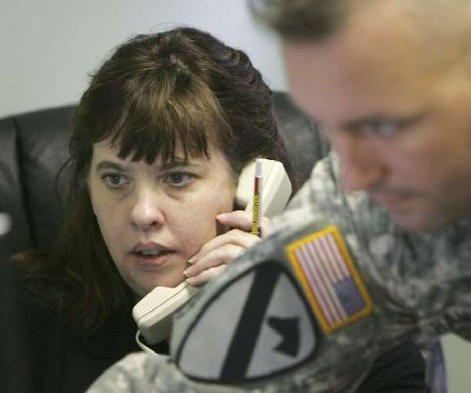 Darcy Woodke, a family assistance coordinator for the U.S. military, works the phone Dec. 6 at her office in the Oregon National Guard armory in Eugene, Ore. Photo: RICK BOWMER, ASSOCIATED PRESS