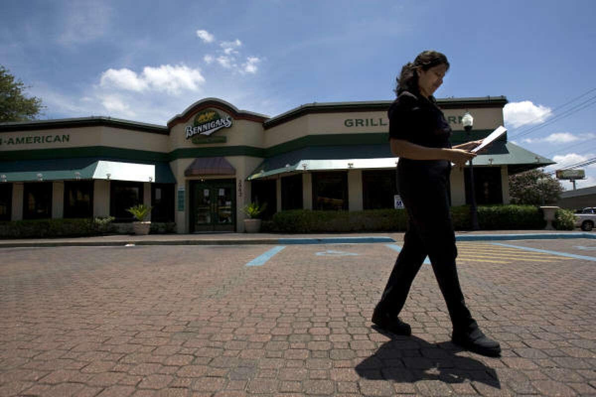 Ramey Thomas, of Houston, an occasional diner at the Bennigan's restaurant on the corner of Kirby and the Southwest Freeway, walks back through the empty parking lot to her car after seeing the location was closed today.