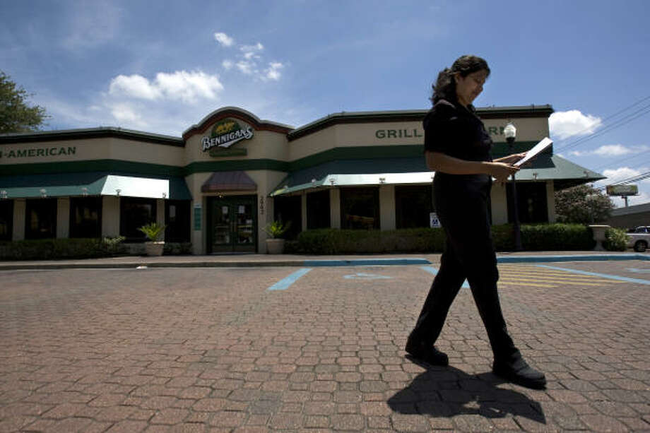 Ramey Thomas, of Houston, an occasional diner at the Bennigan's restaurant on the corner of Kirby and the Southwest Freeway, walks back through the empty parking lot to her car after seeing the location was closed today. Photo: Johnny Hanson, Chronicle