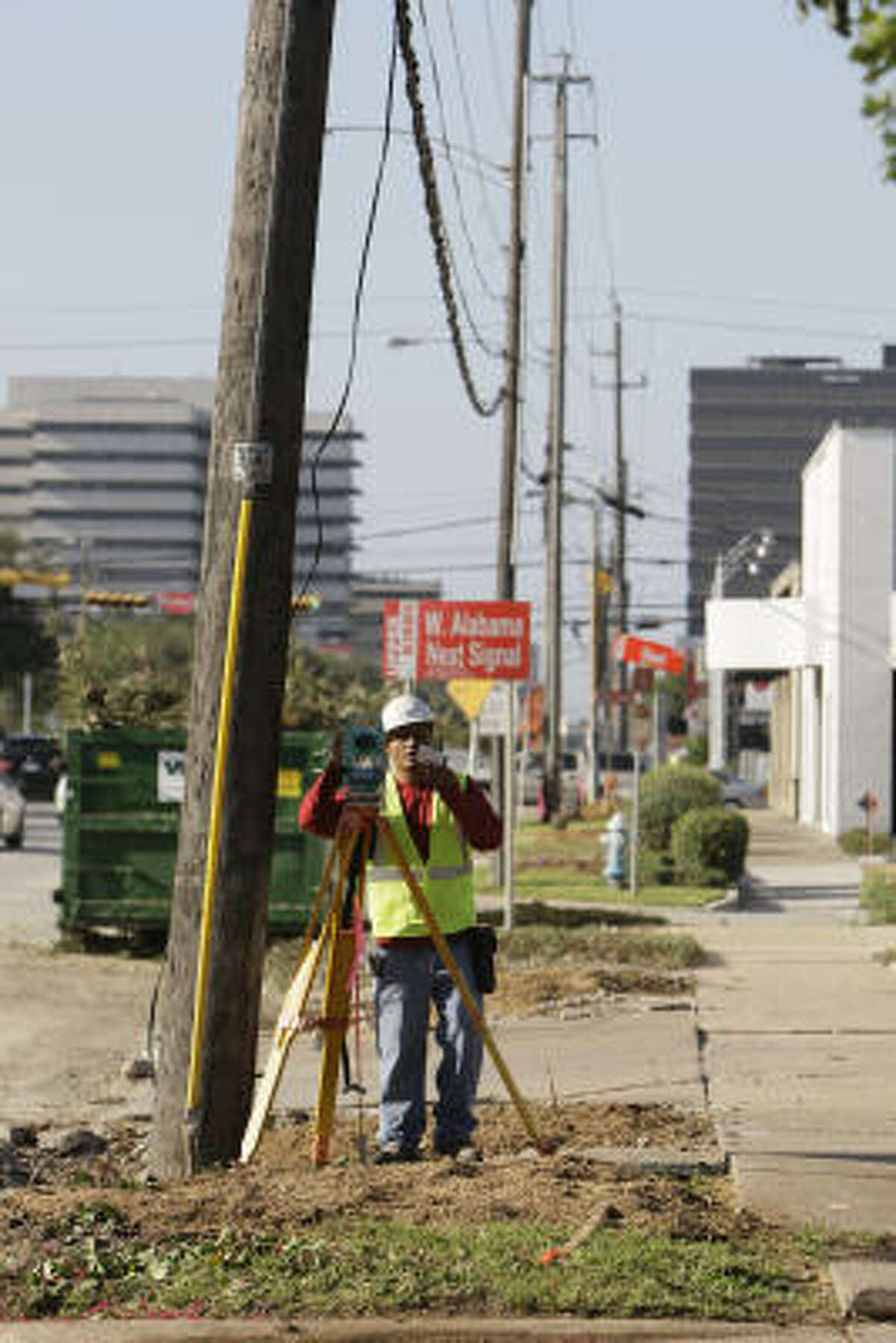 A surveyor works along Kirby near West Alabama where the trees were recently removed on the west side of Kirby between Richmond and Kipling Tuesday, July 29, 2008, in Houston. ( Melissa Phillip / Chronicle )