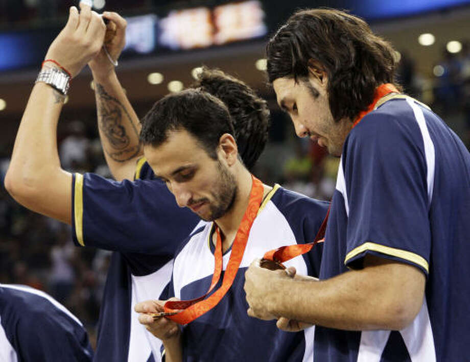 Manu Ginobili, left, and Luis Scola, right, look at their bronze medals following Argentina's win over Lithuania. Photo: Eric Gay, AP