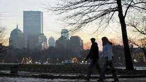 A couple walks through Boston Common past the Boston skyline at dusk, Saturday, Dec. 29, 2007. (AP Photo/Lisa Poole)