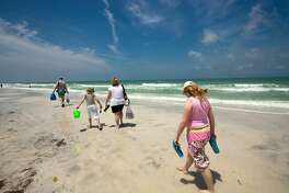 Tourists stroll the main beach at Caladesi Island State Park, a barrier island in the Gulf of Mexico on Florida's west coast.