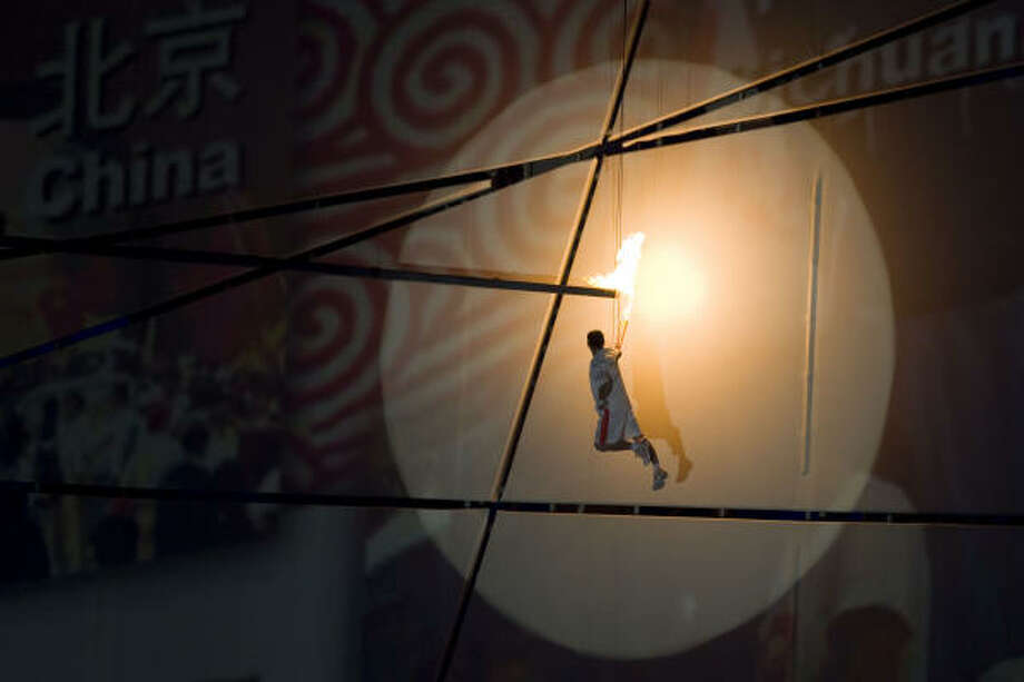 Li Ning does a high-wire act for the crowd while lighting the Olympic flame at the 91,000-seat Bird's Nest in Beijing. Photo: Smiley N. Pool, Chronicle
