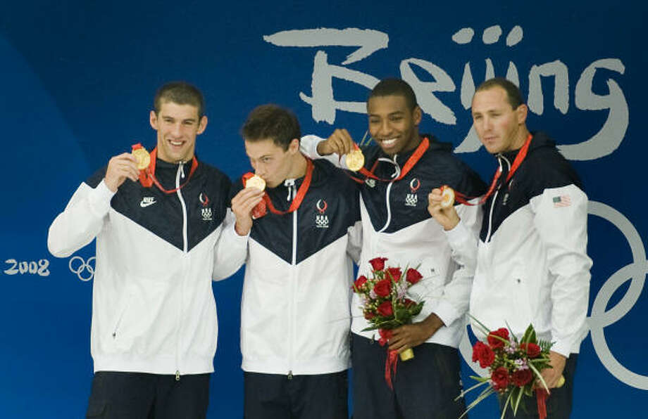 It took a world-record effort from Michael Phelps, left, and the 400 men's relay team to win gold on Monday. Photo: Smiley N. Pool, Chronicle Olympic Bureau