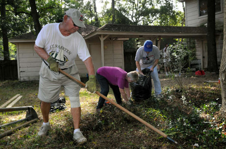 Tom Schafer, left, joined by Rosemary Jenner and Robert Doyand, all of Kingwood, clean the backyard of a Kingwood resident whose home was in need of cleaning and repair. Three crews of neighbors volunteered to fix up the house in an effort that will hopefully influence other neighbors to join in. Photo: Jerry Baker