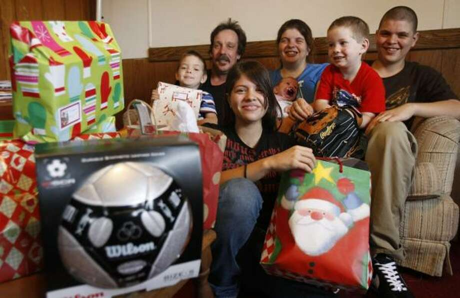 The Schultz family sits surrounded by Christmas presents on Wednesday. From left: Dillion, 5; Ron, 48; Monica, 16; Mia, 40, who holds Alexis, 1 month; Damian, 4; and Michael, 15. Photo: JULIO CORTEZ, CHRONICLE