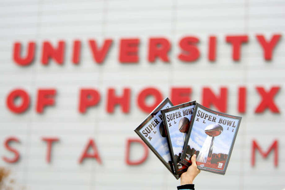 A vendor holds up programs in front of University of Phoenix Stadium before Super Bowl XLII. Photo: Donald Miralle, Getty Images