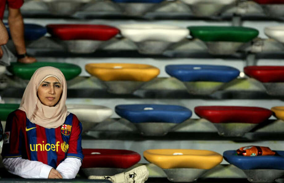 A veiled woman, wearing the shirt of Barcelona FC, attends the FIFA Club World Cup football match between Barcelona and Atlante in Abu Dhabi on December 16, 2009. AFP PHOTO/MARWAN NAAMANI Photo: MARWAN NAAMANI, AFP/Getty Images