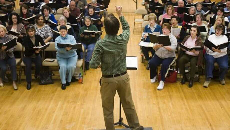 Kevin Klotz conducts a rehearsal of the choir that will perform at Tuesday and Wednesday services at the new Co-Cathedral of the Sacred Heart. Photo: SMILEY N. POOL, CHRONICLE