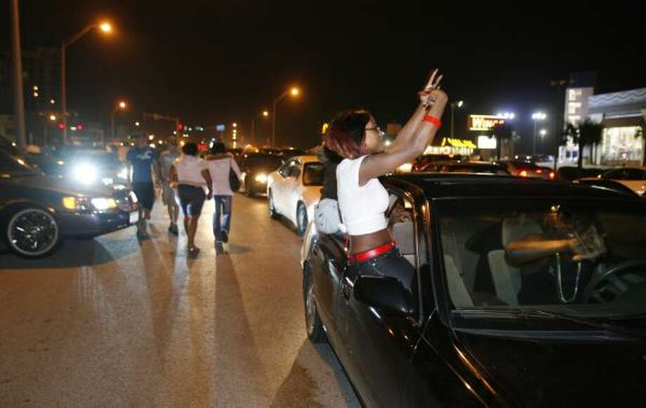 Revelers cruise Seawall Boulevard in Galveston on Sunday, following a free rap concert, which ended with 12 arrests and traffic gridlock that took officers four hours to disperse. Photo: JENNIFER REYNOLDS, GALVESTON COUNTY DAILY NEWS