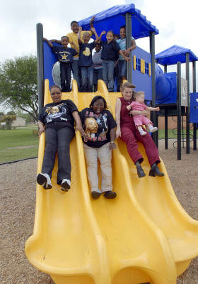 Geraldine Sam, left, Sharyl Allen and Ally Morphis slide down as kids cheer on the new playground equipment donated by Morphis through Oprah's Big Give at Sims Elementary in La Marque. Photo: Kim Christensen, For The Chronicle
