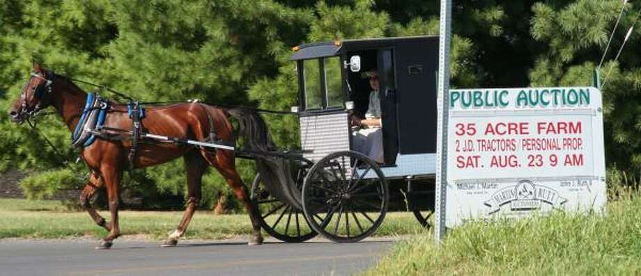 While some Amish decide to stay in Pennsylvania — such as this horse-and-carriage driver in New Holland — others are seeking out new areas for affordable farmland. According to one study, Amish settlements have been established in seven new states since the early 1990s. Photo: VINNY TENNIS, ASSOCIATED PRESS