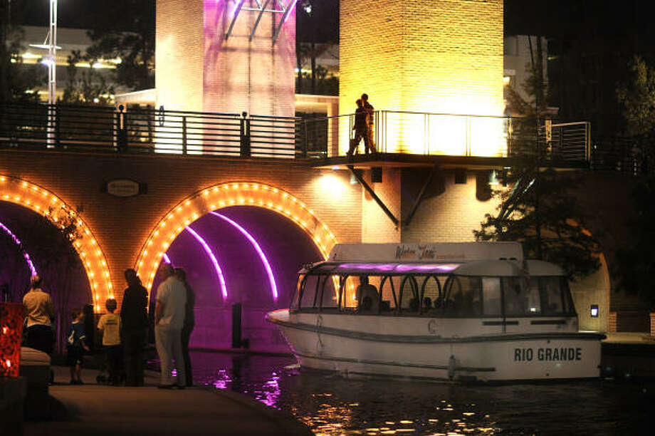 A boat taxi goes under the Waterway Avenue bridge as visitors enjoy the activities along The Woodlands Waterway. Photo: David Hopper, For The Chronicle