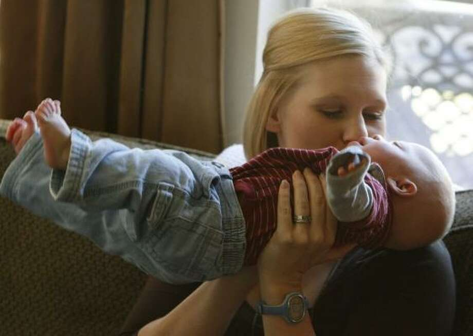 Kim Stroh kisses her 5-month-old son Blake, who with his twin Owen, suffered from twin-to-twin transfusion syndrome and underwent a revolutionary surgery at Texas Children's Hospital. The condition, if left untreated, typically claims the life of at least one and sometimes both babies. Even with the surgery, it was uncertain if both twins would survive. Photo: JULIO CORTEZ, CHRONICLE