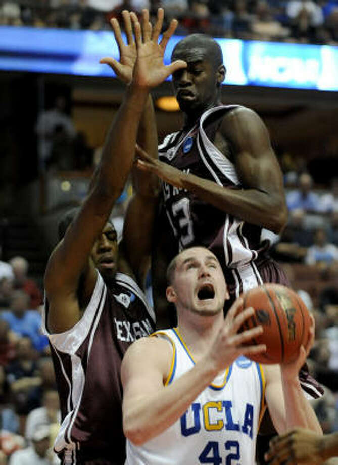 UCLA's Kevin Love looks to avoid A&M's Chinemelu Elonu and Josh Carter on his way to the basket during the first half. Photo: Kevork Djansezian, AP