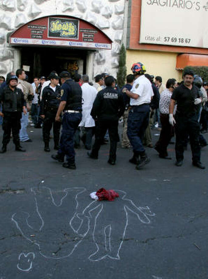 Officials gather outside a nightclub in Mexico City, on Friday, June 20, 2008, after at least 12 people were trampled to death during a police raid. Photo: STR, AFP/Getty Images