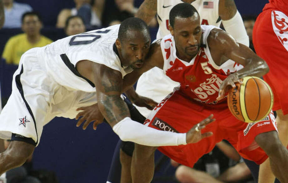 Kobe Bryant, who carried the U.S. team, battles for a loose ball with Russia's Jon Robert Holden. Photo: Eugene Hoshiko, AP